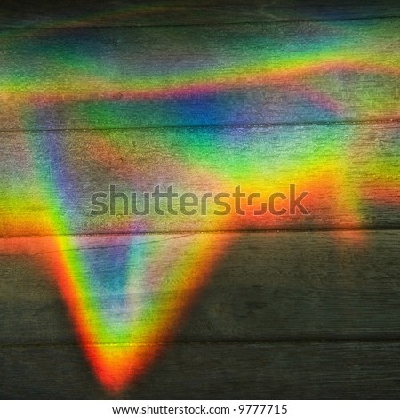 Abstract design of rainbow color prism on wood paneling.