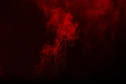 Abstract design of red powder cloud against dark background.