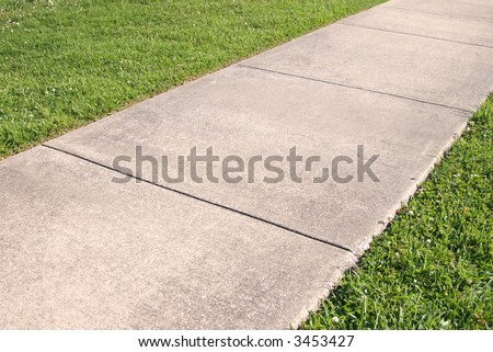 Abstract detail of a concrete sidewalk and grass
