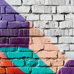 Abstract detail of brick wall with fragment of colorful graffiti. Urban Art close-up. With place for your text, for background use. Aerosol city design
