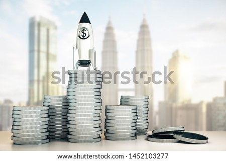 Abstract dollar rocket on silver coins stack. Blurry Kuala Lumpur city background. Startup and venture capital concept. 3D Rendering  ストックフォト ©