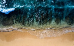 Abstract drone view taken directly from above of some tidal waves breaking along the shoreline of a beach in Bali Indonesia.