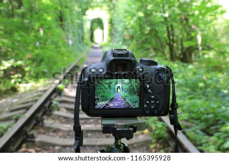 Abstract DSLR Camera on railway in forest #1165395928