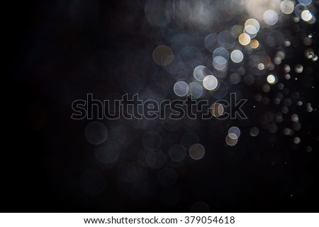Abstract elegant glitter sparkle bokeh defocused on black background