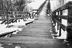 abstract empty old wooden bridge closeup and with snow in winter or spring on a black and white photo of a monochrome tone