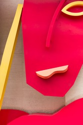 Abstract Face of a Woman (Handbag Heads, Bruce McLean). This is a piece of art publicly displayed just off Oxford Street in London. It is made of metal and painted in bright yellow and red colours.