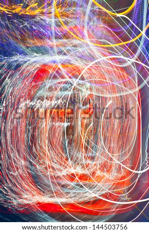 Abstract festive background - bright red, white, blue, yellow twisted lights and lines
