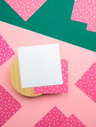 Abstract flatlay,close up top view square note sheets on round wooden base,dark green diagonal paper background,corners of pink paper with white polka dots around perimeter.Design pattern copy space.