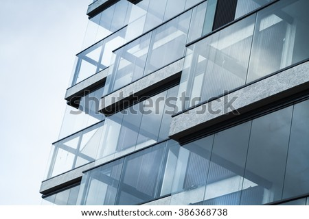Abstract fragment of modern architecture, walls made of glass and concrete. Blue tonal filter photo effect #386368738