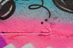Abstract fragment of wall with detal of graffiti, old chipped paint, scratch, grunge texture. Aerosol design, pink-blue shades. Modern background, banner design