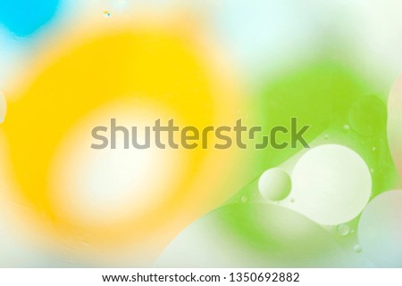 Abstract gentle blurred background. The texture of the liquid with circles and drops of green, yellow, blue and white. Cropped shooting, macro, horizontal, nobody, free space for text. #1350692882