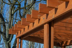 Abstract geometric composition of brown wooden planks against a blue sky. Fragment of a gazebo in a city park. Selective focus.