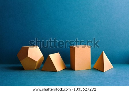 Abstract geometric figures. Three-dimensional dodecahedron pyramid tetrahedron cube rectangular objects on blue background. Yellow color Platonic solids still life background.