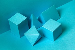 Abstract geometrical figures still life composition. Three-dimensional prism pyramid rectangular cube objects on turquoise background. Platonic solids figures,  selective focus.