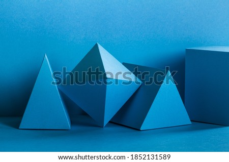 Photo of  Abstract geometrical figures still life composition. Three-dimensional prism pyramid rectangular cube objects on turquoise background. Platonic solids figures,  selective focus.