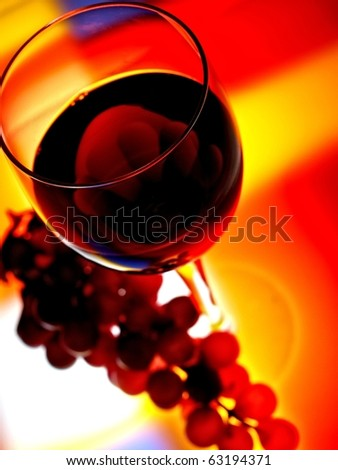 Abstract  glassware background design of wine glass and grapes  on multicolored  background.