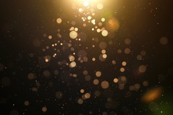 Abstract glittering gold with bokeh and dust effect . Black background .