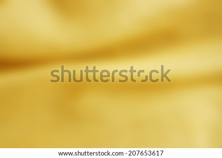 Abstract gold background luxury cloth, liquid wave or wavy folds of grunge silk texture satin, gold background may use for wedding background.