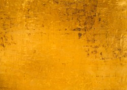 Abstract golden background for art decor with matte texture and variation shades of Fortuna Gold color. Metallic paint on vintage wall, gilded and aged effect with brown stains on surface.