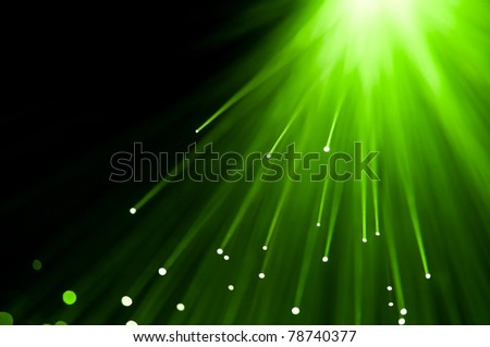 Abstract green fibre optic light strands against a black background.