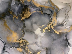Abstract grey art with gold — black and white background with beautiful smudges and stains made with alcohol ink and golden pigment. Fluid art texture resembles watercolor or aquarelle.
