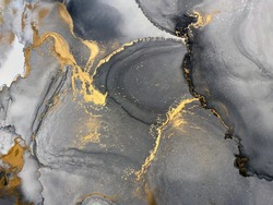 Abstract grey art with gold — black and white background with beautiful smudges, stains and splashes made with alcohol ink. Fluid art texture resembles smoke, stone, marble, watercolor or aquarelle.