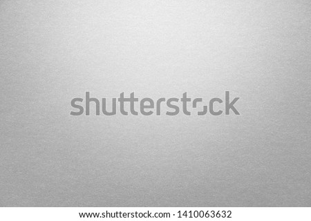 Abstract grey glossy paper texture background or backdrop. Empty gray cardboard or shiny paperboard for decorative design element. Simple grainy textured surface for journal template presentation
