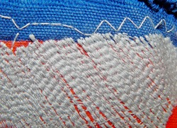 Abstract grunge blue red background fabric flag quilted with white thread.The texture of the darning threads.Decorative textile wallpaper design.