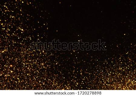 Abstract holiday background, gold Stardust on black. Sequins in focus and out of focus.