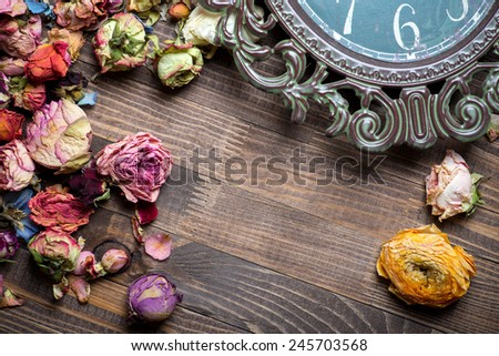 Abstract holiday frame with rose petals and dried flowers on old wooden plates.