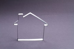 Abstract house design concept. Metallic frame outline of a house on grey background.