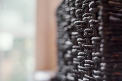 Abstract image, close up view of a black woven wicker basket opposite of a bright bokeh window.