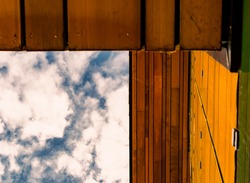 Abstract image of a blue sky with clouds, wooden yellow roof and wall