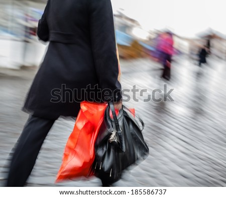 Abstract image of a woman walking down the street in the rain with a red package and black bag.