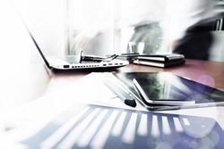 Abstract Image of business documents on office table with smart phone and digital tablet and man working in the background