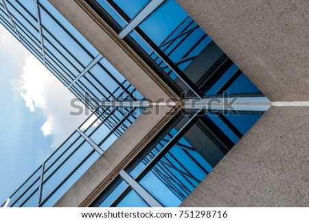 Abstract image of looking up at modern glass and concrete building. Architectural exterior detail of industrial office building. Industrial art and detail.