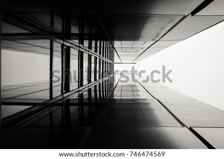 Abstract image of looking up at modern glass building. Architectural exterior detail of industrial office building. Industrial art and detail.