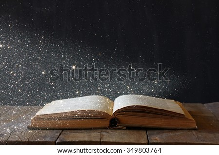 abstract image of open antique book on wooden table. selective focus. retro filtered with glitter overlay