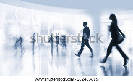abstract image of people in the lobby of a modern business center with a blurred background  and a blue tonality