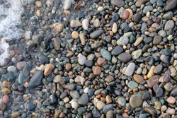 Abstract image of the water ripples over the stone pebbles in the Mediterranean Sea. Gray abstract background