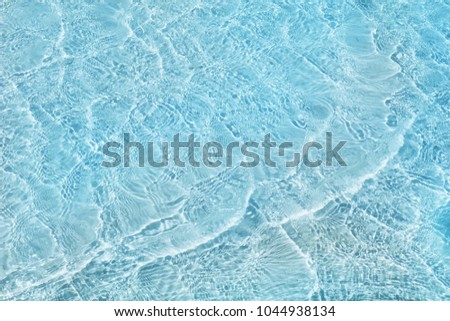 Abstract image of top view of shiny wave of clear blue sea water over sand beach, for beautiful background decoration of summer time