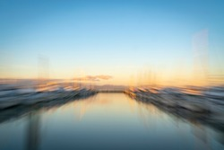 Abstract impressionist effect zoom blur Tauranga Marina boats and piers reflected in calm water at sunrise.