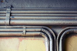 Abstract industrial background, group of bent vintage electrical conduits mounted on a concrete wall.  Old style toned, instagram photo filter effect