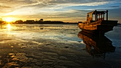 Abstract landscape of sea when sunset, tide going out, sun go down, sunbeam shine on wooden fishing boat that reflect on surface water of beach, colorful sky at evening scene