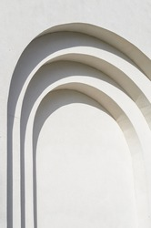 Abstract lines of arches in a white plastered wall. Abstract background with flowing lines. Architecture backdrop