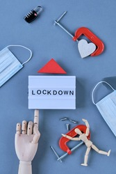 abstract lockdown symbols are laid around the captain 'LOCKDOWN' such as locks lose screws, a heart in a clamp and a figure in a clamp and a facemask