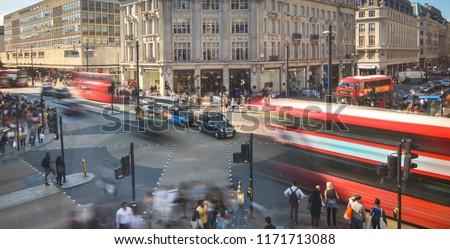 Abstract London street scene with motion blurred double decker buses and crowds of people