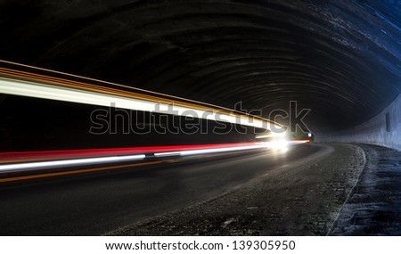 Abstract long exposure car light trails in tunnel