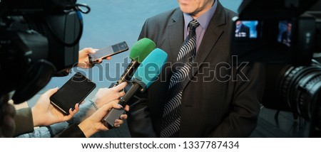 Abstract man in a suit and tie speaks to reporters and video cameras. Female hands hold microphones, voice recorders and mobile phones to record sound. Interview, report, media.