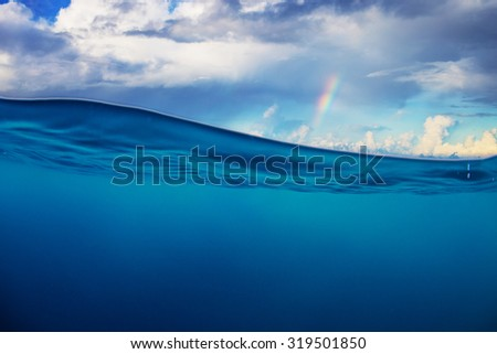 Abstract marine design template. Cloudy sky with rainbow splitted by waterline. Blue deep ocean. #319501850